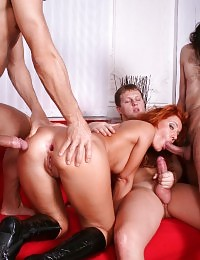 Redhead chick lets three studs stuff her sex holes
