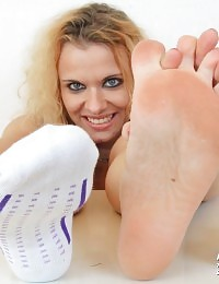 The blonde female Anita Girlie oils her feet and gives footjobs